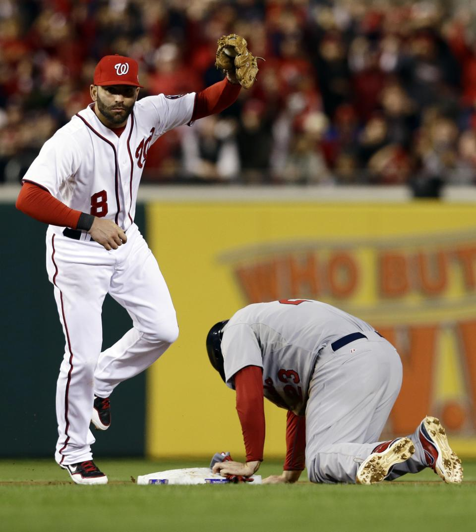 Washington Nationals second baseman Danny Espinosa, left, holds up his glove with the ball after tagging out St. Louis Cardinals' David Freese on a steal attempt in the second inning of Game 5 of the National League division baseball series Friday, Oct. 12, 2012, in Washington. (AP Photo/Alex Brandon)