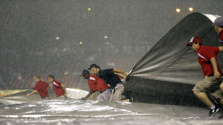 Members of the grounds crew rush to put the tarp on the field at the start of a rain delay during the ninth inning of a baseball game between the St. Louis Cardinals and the Kansas City Royals on Thursday, May 30, 2013, in St. Louis. (AP Photo/Jeff Roberson)