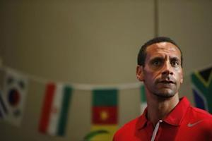 Former Manchester United player Rio Ferdinand looks on in front of flags of nations in the World Cup during an event in Singapore