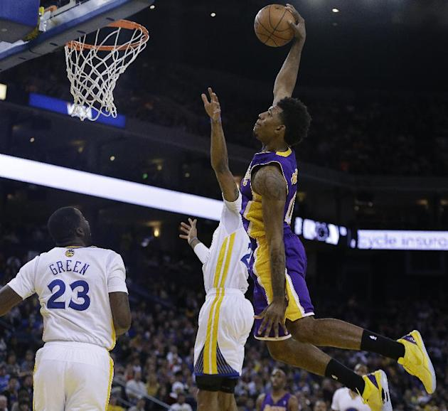 Los Angeles Lakers' Nick Young drives to score over Golden State Warriors' Kent Bazemore and Draymond Green (23) during the second half of an NBA basketball game, Saturday, Dec. 21, 2013, in O