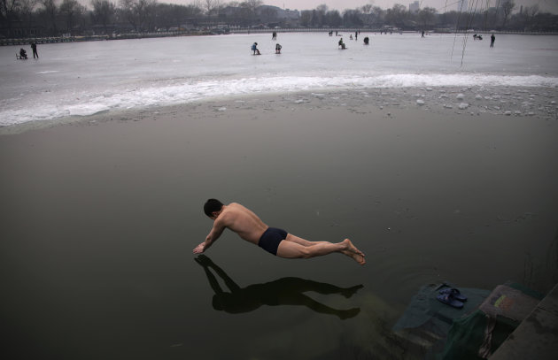 A swimmer dives into the icy water of the Houhai Lake in central Beijing