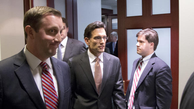 Majority Leader Eric Cantor from Virginia, center, departs after a House Republicans meeting on Capitol Hill, Thursday, Dec. 20, 2012 in Washington. Confronted with a revolt among the rank and file, House Republicans abruptly put off a vote Thursday night on legislation allowing tax rates to rise for households earning $1 million and up.(AP Photo/Alex Brandon)