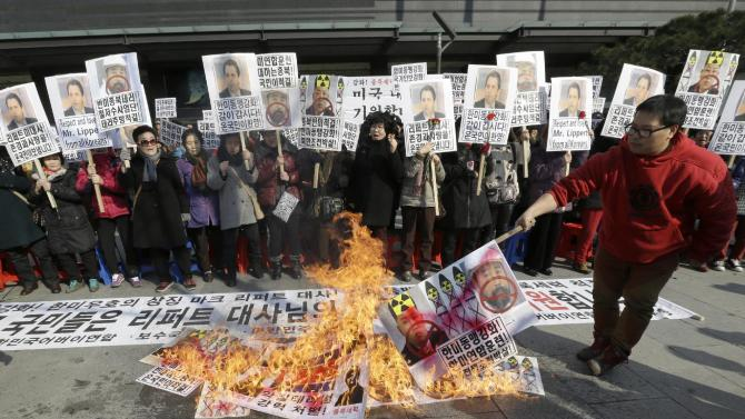 "A South Korean conservative activist burns a mock North Korean flag, portraits of North Korean leader Kim Jon Un and Kim Ki-jong, the suspect of slashing U.S. Ambassador Mark Lippert, during a rally demanding quick recovery of Lippert near the U.S. embassy in Seoul, South Korea, Friday, March 6, 2015. Thursday's attack, which prompted rival North Korea to gloat about ""knife slashes of justice,"" left deep gashes and damaged tendons and nerves. (AP Photo/Ahn Young-joon)"