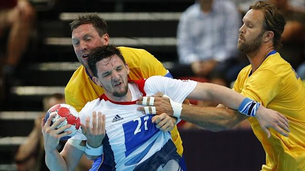 Britain's Christopher McDermott (C) struggles to get past Sweden's defence in their men's handball Preliminaries Group A match at the Copper Box during the Olympics (Reuters)