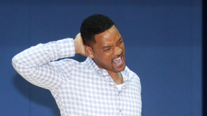 Actor Will Smith stretches before meeting some of the Great Britain Olympic team at Ethos gym in London, Wednesday, May 16, 2012. (AP Photo/Jim Ross)
