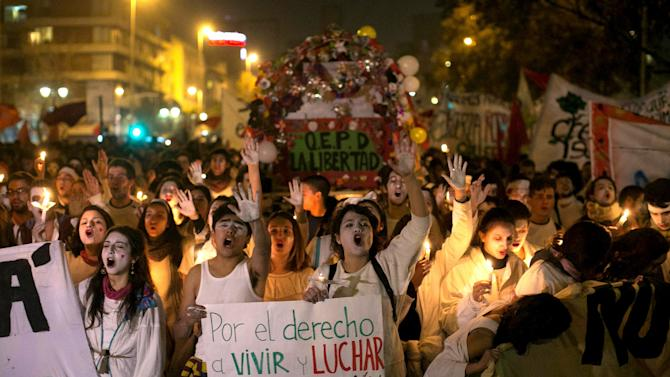 Demonstrators shout slogans as they attend a rally against police violence in Santiago