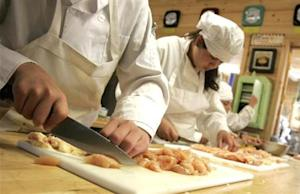 Children cut chicken in the kitchen of the Vermont Kids Culinary Academy during a residential cooking summer camp in Highgate