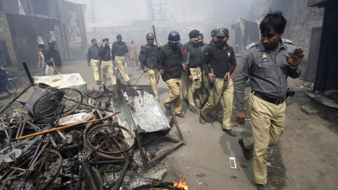 Pakistani police officers walk past belongings of Christian families, which were burnt by an angry mob, in Lahore, Pakistan, Saturday, March 9, 2013. A mob of hundreds of people in the eastern Pakistani city of Lahore attacked a Christian neighborhood Saturday and set fire to homes after hearing accusations that a Christian man had committed blasphemy against Islam's prophet, said a police officer. (AP Photo/K.M. Chaudary)