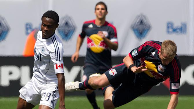 Vancouver Whitecaps' Gershon Koffie, left, forces New York Red Bulls' Jan Gunnar Solli off the ball during the first half of an MLS soccer match in Vancouver, B.C., on Saturday, May 28, 2011. (AP Photo/The Canadian Press, Darryl Dyck)