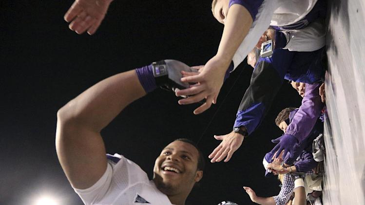 Players from Kansas State, including Keenan Taylor (79), celebrate their victory with fans following an NCAA college football game against West Virginia in Morgantown, W.Va., Saturday, Oct. 20, 2012. Kansas State won 55-14. (AP Photo/Christopher Jackson)
