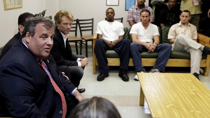 New Jersey Gov. Chris Christie, left, sits with singer Jon Bon Jovi, second from left, while visiting patients at the Turning Point drug rehab program at Barnert Medical Arts Complex, Thursday, May 2, 2013, in Paterson, N.J. During the visit, Christie signed into law a good Samaritan bill intended to assure that a fear of prosecution doesn't get in the way of medical help for overdose victims. The New Jersey law will shield from prosecution both overdose victims and those seeking medical help for them if they act in good faith. Bon Jovi's daughter suffered an apparent drug overdose on heroin in a dorm at Hamilton College in upstate New York last year. (AP Photo/Julio Cortez)