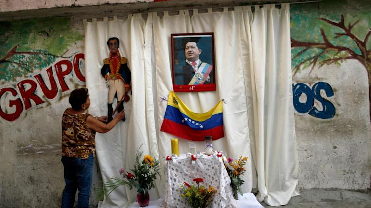 A woman places an image of Venezuela's independence hero Simon Bolivar on an altar set up on a sidewalk in honor of late President Hugo Chavez, whose picture hangs on the curtain, along a street where a procession will pass tomorrow to transfer Chavez's body to a military museum in Caracas, Venezuela, Thursday, March 14, 2013.  (AP Photo/Rodrigo Abd)