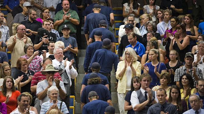 Firefighters are given a standing ovation as they enter the auditorium for a memorial service for 19 firefighters of the Granite Mountain Hotshot Crew, Monday, July 1, 2013 in Prescott, Ariz. (AP Photo/The Arizona Republic, Tom Tingle)