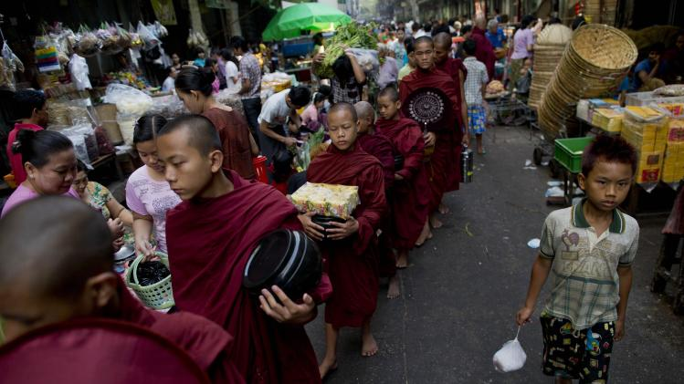 Buddhist monks walk through a street market expecting alms in Yangon, Myanmar, Tuesday, March 26, 2013. Myanmar's government warned Monday that religious violence could threaten democratic reforms after anti-Muslim mobs rampaged through three more towns in the country's predominantly Buddhist heartland. The mobs destroyed mosques and burned dozens of homes over the weekend despite attempts by the government to stem the nation's latest outbreak of sectarian violence. (AP Photo/Gemunu Amarasinghe)