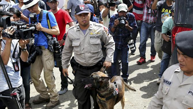 An Indonesian police officer with his dog stands guard at Wijayapura port in Cilacap, Central Java, Indonesia, Monday, April 27, 2015. Indonesia notified nine foreigners and a local man convicted of drug trafficking that their executions will be carried out within days, ignoring appeals by the U.N. chief and foreign leaders to spare them. (AP Photo/Tatan Syuflana)