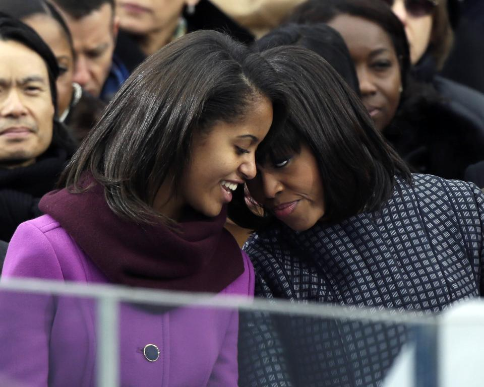 First lady Michelle Obama speaks with her daughter Malia at the ceremonial swearing-in for President Barack Obama at the U.S. Capitol during the 57th Presidential Inauguration in Washington, Monday, Jan. 21, 2013. (AP Photo/Pablo Martinez Monsivais)