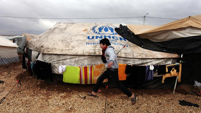 A Syrian refugee boy runs to his family tent at Zaatari Syrian refugee camp, near the Syrian border in Mafraq, Jordan, Tuesday, Jan. 8, 2013. Syrian refugees in a Jordanian camp attacked aid workers with sticks and stones on Tuesday, frustrated after cold, howling winds swept away their tents and torrential rains flooded muddy streets overnight. Police said seven aid workers were injured. (AP Photo/Mohammad Hannon)