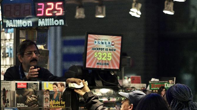 A vendor, left, receives money for a lottery purchase on Friday, Nov. 23, 2012 in New York.  The jackpot for Powerball's weekend drawing has climbed to $325 million, the fourth-largest in the game's history.  Powerball organizers say this is the first run-up to a large jackpot that's fallen over a major holiday.  (AP Photo/Bebeto Matthews)