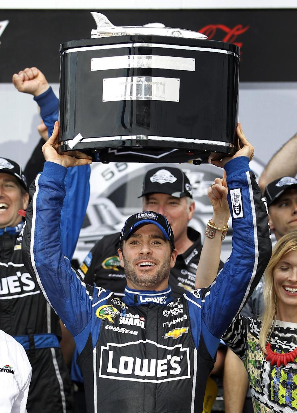 Jimmie Johnson holds up his trophy next to his wife Chandra, right, after winning the Daytona 500 NASCAR Sprint Cup Series auto race, Sunday, Feb. 24, 2013, at Daytona International Speedway in Daytona Beach, Fla. (AP Photo/Terry Renna)