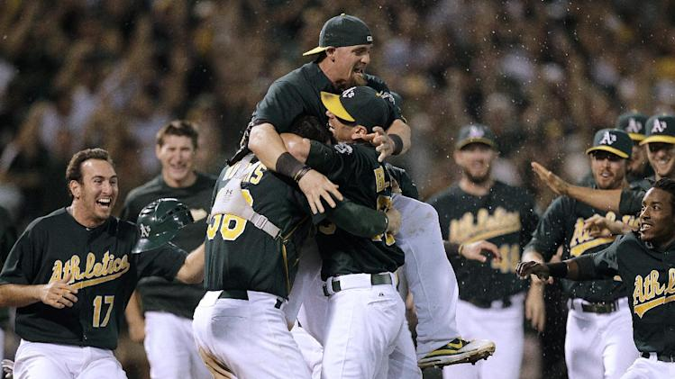 Oakland Athletics players celebrate after clinching a wild card berth in the American League at the end of a baseball game against the Texas Rangers on Monday, Oct. 1, 2012, in Oakland, Calif. (AP Photo/Ben Margot)