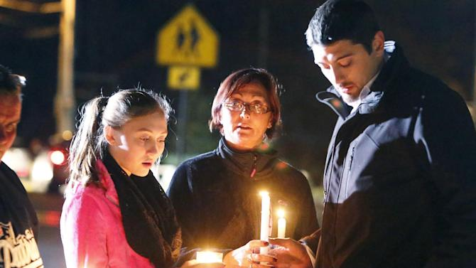 Parents and Danvers High School students hold candlelight vigil to mourn the death of Colleen Ritzer, a 24-year-old math teacher at Danvers High School, on Wednesday, Oct 23, 2013, in Danvers, Mass. Ritzer's body was found in woods behind the school, and Danvers High School student Philip Chism, 14, who was found walking along a state highway overnight, was charged with killing her. (AP Photo/ Bizuayehu Tesfaye)