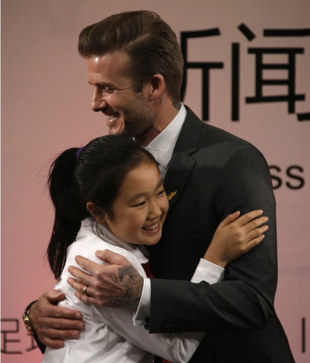 Former England captain David Beckham hugs a student after she presented him a pin during a news conference at a primary school in Beijing