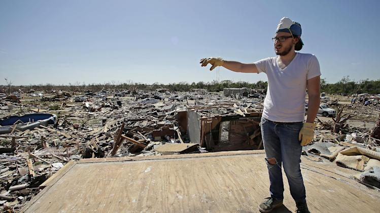 Cody Cannon looks at tornado destruction in his neighborhood from the second floor of his parent's home that once was his bedroom Wednesday, May 22, 2013, in Moore, Okla. Cleanup continues two days after a huge tornado roared through the Oklahoma City suburb, flattening a wide swath of homes and businesses. (AP Photo/Charlie Riedel)