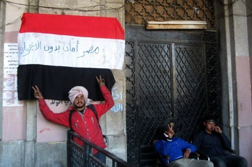 &lt;p&gt;An Egyptian protester flashes the sign of victory in front a national flag on which is written in Arabic &quot;Egypt is moor safe without Muslim Brotherhoods in front of the Mugamma, Cairo&#39;s main administrative building on February 24, 2013. In Cairo on Sunday, protesters blocked the doors to the main administrative building as part of a growing campaign of civil disobedience around the country&lt;/p&gt;