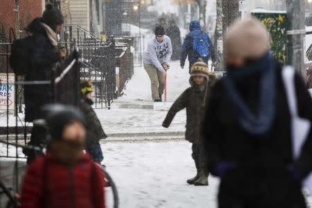 A man shovels snow off of the sidewalk during a snow storm in New York