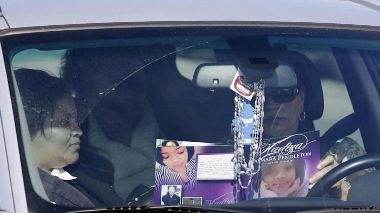 Mourners read a program for the funeral of Hadiya Pendleton inside a car of outside the Greater Harvest Missionary Baptist Church after the funeral service of Hadiya Pendleton Saturday, Feb. 9, 2013, in Chicago. Hundreds of mourners and dignitaries including first lady Michelle Obama packed the funeral service Saturday for a Chicago teen whose killing catapulted her into the nation's debate over gun violence. (AP Photo/Nam Y. Huh)