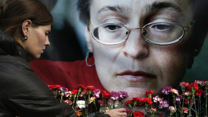 FILE- A woman places flowers before a portrait of slain Russian journalist Anna Politkovskaya, in Moscow, in this file photo dated Wednesday, Oct. 7, 2009.  Investigator Petros Garibian who led the murder probe said in an interview published Friday Nov. 9, 2012, that Politkovskaya was gunned down in the elevator of her Moscow apartment building, killed for her criticism of Russian officials, the Kremlin and its policies in Chechnya.(AP Photo/Pavel Golovkin, File)