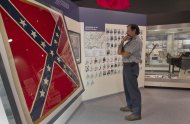"Confederate Memorial Park Director Bill Rambo looks at a display in the museum at the park in Mountain Creek, Ala., Tuesday, July 19, 2011. More than 60,000 Confederate veterans came home to Alabama after the Civil War, and residents are still paying a tax that supported them 150 years after the fighting began. The tax now pays for the park, which is located on the same 102-acre tract where elderly veterans used to stroll. The tax once brought in millions for Confederate pensions, but lawmakers sliced up the levy and sent money elsewhere as the men and their wives died. No one has seriously challenged the continued use of the money for a memorial to the ""Lost Cause,"" although a long-serving black legislator wants to eliminate state funding for the park. (AP Photo/Dave Martin)"