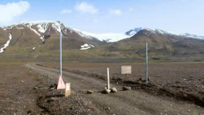 """In an in an image from an Aug. 19, 2014 video, a sign is posted on the road next to Bardarbunga, a subglacial stratovolcano located under Iceland's largest glacier. On Saturday, Aug. 23, 2014, Iceland closed airspace over the Bardarbunga volcano on Saturday after the Meteorological Office said an eruption had begun under the ice of Europe's largest glacier. The English portion of the sign reads, """"""""Uncertainty phase due to unrest in Bardarbunga"""". (AP Photo/Courtesy Channel 2 Iceland)"""