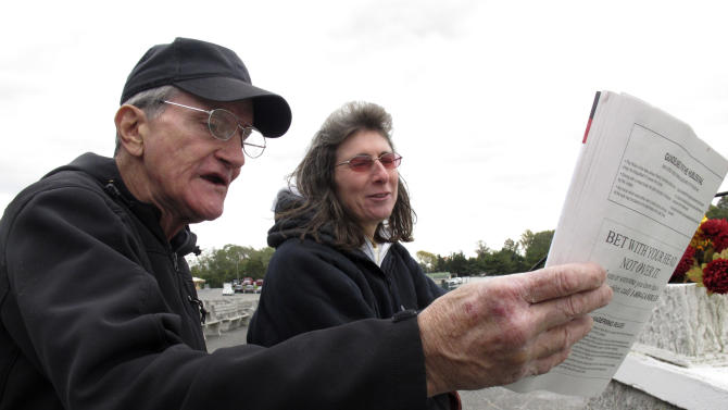 In this Oct. 21, 2011 photo, Phil Gartner, left, of Farmingdale, N.J., and Patricia DiCenzo, of Boonton, N.J., check the program before the last race of the day at Freehold Raceway in Freehold N.J. They both support a non-binding referendum on the New jersey ballot in November asking voters whether they favor legalizing sports betting at the state's racetracks and casinos. (AP Photo/Wayne Parry)