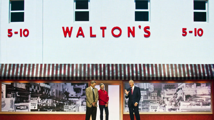 Jim Walton, left, Alice Walton, left center, and Robson Walton, right, chairman of the board of directors of Walmart Stores Inc., stand before a video board showing the original Five and Dime store owned by their father, the late Sam Walton, during the Walmart shareholders' meeting in Fayetteville, Ark., Friday, June 1, 2012. (AP Photo/April L. Brown)