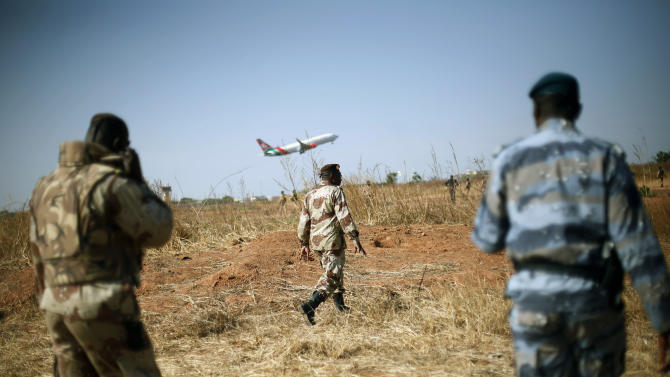 """Mali National Guard soldiers stand guard on the military side of  Bamako's airport Wednesday Jan. 16, 2013,  as a commercial jet takes off during a joined visit to French and Malian troops by Mali's President  Dioncounda Traore and French Ambassador to Mali  Christian Rouyer. French troops pressed northward in Mali toward territory occupied by radical Islamists on Wednesday, military officials said, announcing the start of a land assault that will put soldiers in direct combat """"within hours.""""(AP Photo/Jerome Delay)"""