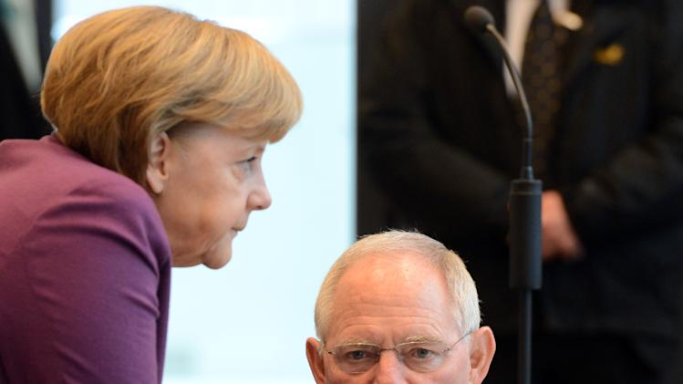 German chancellor Angela Merkel and Finance Minister Wolfgang Schaeuble, right, talk at the beginning of the special parliamentary meeting of the Christian Democratic party in Berlin, Germany, Friday, March 22, 2013. By rejecting an EU bailout and turning to Russia for help, Cyprus has exposed the growing frustration and dwindling solidarity within the European Union, a bloc meant to bring the continent closer together after World War II. (AP Photo/dpa,  Soeren Stache)
