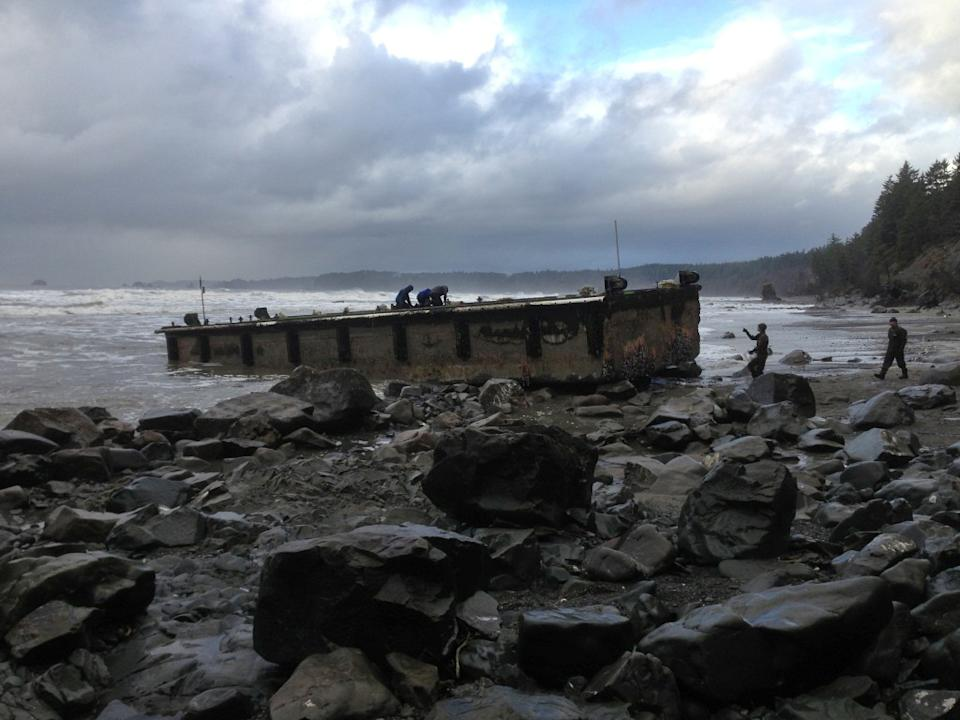 Members of the Washington tsunami debris experts team inspect a dock Friday Dec. 21, 2012 that apparently floated from Japan after last year's tsunami and just washed ashore on a Washington beach near Forks Tuesday. (AP Photo/Washington Dept. of Fish & Wildlife)