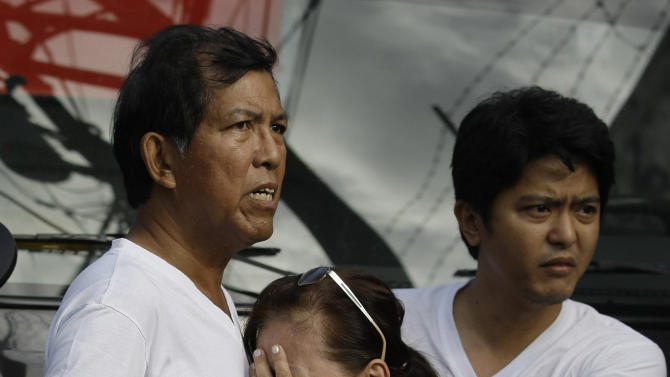 A Filipino family grieves as they hear news of relatives that were trapped during a fire along a row of apartments in suburban Quezon City, north of Manila, Philippines on Christmas day Tuesday Dec. 25, 2012. Fire Officer 3 Francisco Mabunga said about 6 people died when a row of houses went up in flames early Christmas day Tuesday. Another fire hit a slum area in San Juan city leaving some 2,000 families homeless. (AP Photo/Aaron Favila)