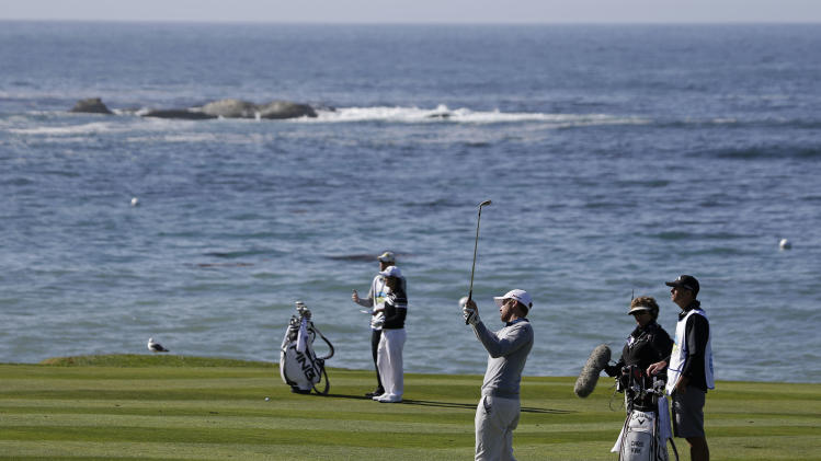 Chris Kirk, foreground, follows his shot from the fairway up to the fourth green of the Pebble Beach Golf Links during the final round of the AT&T Pebble Beach Pro-Am golf tournament on Sunday, Feb. 10, 2013, in Pebble Beach, Calif. (AP Photo/Eric Risberg)