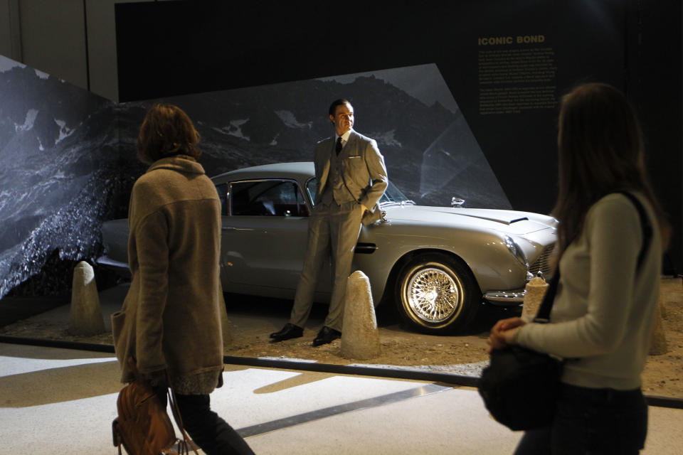 Visitors look at as they walk by a James Bond's Aston Martin DB5 used in the film 'GoldenEye' on display in the exhibition 'Designing 007 - Fifty Years of Bond Style' at the Barbican centre in London, Thursday, July 5, 2012. (AP Photo/Sang Tan)