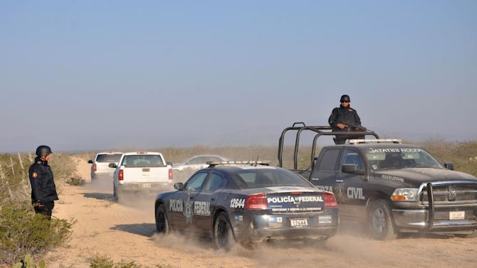 CORRECTS BYLINE TYPO TO VAZQUEZ.- State and federal police drive along a dirt road leading to a ranch near the town of Mina, in northern Mexico, Monday, Jan. 28, 2013. At least eight bodies were found in a well near this ranch on Sunday near the site where 20 people went missing late last week, including members of a Colombian-style band, according to a state forensic official. Officials could not confirm whether the bodies belonged to 16 members of the band Kombo Kolombia and their crew, who were reported missing late last week after playing a private show in a bar in the neighboring town of Hidalgo, north of Monterrey. (AP Photo/Emilio Vazquez)