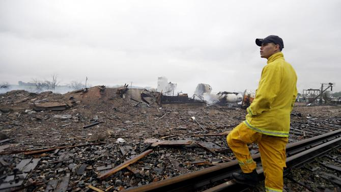 A firefighter stands on a rail line and surveys the remains of a fertilizer plant destroyed by an explosion in West, Texas, Thursday, April 18, 2013.  A massive explosion at the West Fertilizer Co. killed as many as 15 people and injured more than 160, officials said overnight.  (AP Photo/LM Otero)