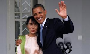 President Obama waves to the media as he embraces Myanmar opposition leader Aung San Suu Kyi at her residence in Yangon on Nov. 19.