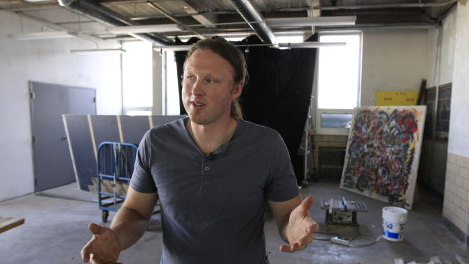 In a photo from July 24, 2012, Carl Goines, a co-founder of 555 Nonprofit Gallery and Studios, speaks in one of the studio's rooms in Detroit. The arts organization has set up shop in a former Detroit Police Department station, where the former lobby now is an airy gallery, detectives' offices now are classrooms and cells with bars still on their doors are places for creativity. (AP Photo/Carlos Osorio)