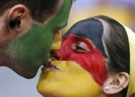 German fans kiss before the Euro 2012 soccer championship Group B match between Germany and Portugal in Lviv, Ukraine, Saturday, June 9, 2012. (AP Photo/Armando Franca)