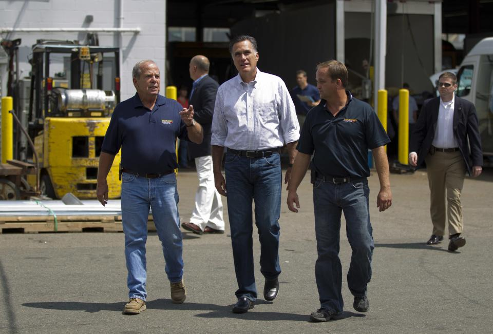 Republican presidential candidate, former Massachusetts Gov. Mitt Romney, center, takes a tour of Middlesex Truck and Coach by owner Brian Maloney, left, and his son Brian Maloney, Jr., during a campaign stop on Thursday, July 19, 2012 in Roxbury, Mass.  (AP Photo/Evan Vucci)