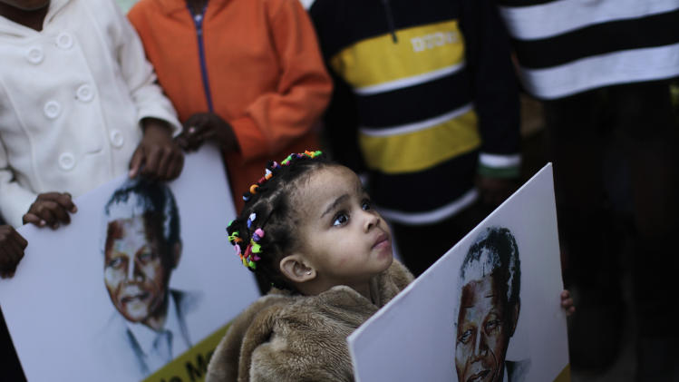 FILE - In this Friday, June 28, 2013, file photo, a South African girl holds a poster showing former South African President Nelson Mandela, while her family and other well wishers gather at the entrance to the Mediclinic Heart Hospital where former South African President Nelson Mandela is being treated in Pretoria, South Africa. Members of Nelson Mandela's family as well as South African Cabinet ministers visited the hospital on Friday where the 94-year-old former president is critically ill. (AP Photo/Muhammed Muheisen, File)