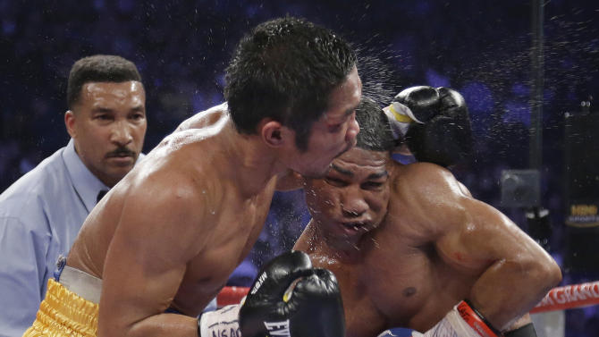 Yuriorkis Gamboa, from Miami, Fla., right, and Michael Farenas, from the Philippines, trade blows in close as referee Tony Weeks looks on during their WBA interim super featherweight title fight Saturday, Dec. 8, 2012, in Las Vegas. (AP Photo/Julie Jacobson)