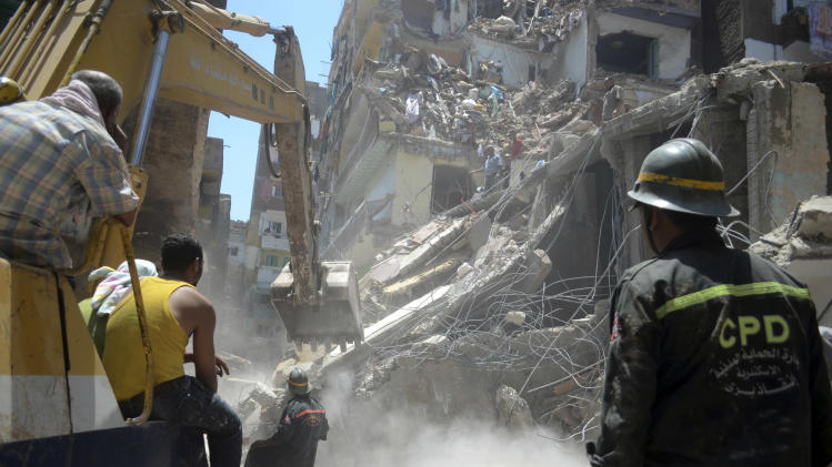 Rescue workers use heavy equipment to remove rubble and look for survivors buried under debris of damaged buildings following the collapse of an 11-story building under construction onto three adjacent buildings that killed at least 10 people in the Gomrouk neighborhood of Alexandria, Egypt, July 15, 2012. With real estate at a premium in big cities like Alexandria and Cairo, developers seeking bigger profits frequently violate planning permits and exceed the number of stories allowed. (AP Photo/Tarek Fawzy)